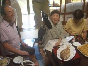 お祝いの品を受取り、満面の笑みを浮かべる長谷川さん
