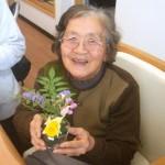 笑顔で作品を見せるおばあちゃん