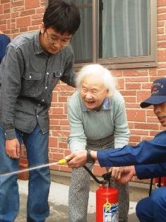 消火器の使い方を教わるお年寄り